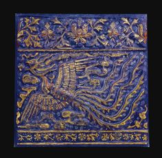 A Large Lajvardina Tile, Persia, 14th Century of square form, moulded and painted in underglaze cobalt blue, overglaze decoration in brownish red, white and gold, with a large flying phoenix with flame-like tail against a scroll ground, narrow floral band below and a border of lotus palmettes above, mounted in a metal frame 37.5cm. square