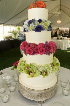 4 tiered wedding cake, with rainbow florals between the layers, for an outdoor Texas wedding. Flowers by Verbena Floral Design www.verbenafloral.com