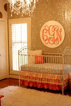 A glamorous coral and gold glitter nursery that our little girl could grow into featuring a glitter wallpaper accent wall and gold polka dot wall decals.