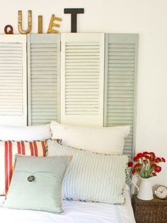 Antique shutters sanded, painted and set up as a headboard. Love. Those letters on top are nice too.