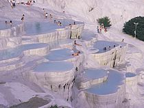 """Pamukkale: An unusual natural and historical site with the sparkling white castle -like cascades, Pamukkale is one of the most important highlights of Turkey, unique in the world. The site is named in Turkish as """"Pamukkale"""", that means """"cotton castle"""", parallel to the glorious and spectacular view of the site. The dazzling white calcareous castles are formed by limestone-laden thermal springs, creating the unbelievable formation of stalactites, potholes and cataracts."""