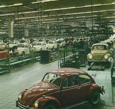 VW Beetle assembly line in 1967. Red car in front is a deluxe US model, cars behind with older style headlights are European 1200 models.