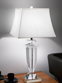 TL879/1167 The Hugo Collection, crystal table lamp. Heavy crystal glass table lamp. Supplied with an off-white silk top fixing shade and decorative crystal glass retaining knob. Please note the lamp is also supplied wih a shade ring if you choose to use a different shade. Shade Type- Self-trimmed tapered square shade. 1 x 60w E27 Lamp not included Height- 69.5cm Width- 34cm x 34cm Base Width- 14cm x 14cm BRAND: Franklite REFERENCE: TL879/1167 AVAILABILITY: 3-4 Working Days **Can be…