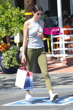 Kendall Jenner wearing Converse Chuck Taylor All Star Low in Optical White, Celine Nano Bag, Ray-Ban Rb3025 Original Aviator Sunglasses, Mother Denim Looker Zip Fray Jeans in Kale and Nasty Gal with My Crew Knit Top
