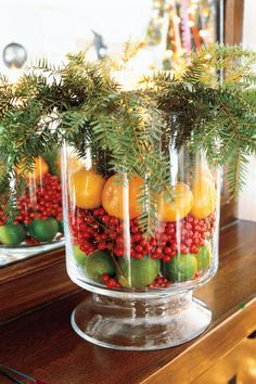 Create an Arrangement with Fruit and Greenery - 101 Fresh Christmas Decorating Ideas - Southernliving. Use a glass hurricane or vase to create an arrangement that will last throughout the Christmas season by filling the jar with a layer of limes, red holly berries, and lemons. Top it off with stems of greenery.