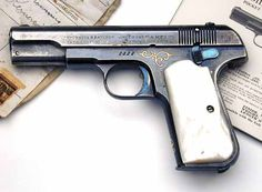The first factory gold inlaid Colt Model 1903 Pocket Hammerless .32 ACP pistol manufactured by Colt. Pistol also has gold inlaid initials and mother of pearl grips.: