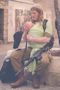 A loving dad and brave soldier--in Israel.  let's see, baby, guitar, rifle, yep. a typical day in Israel. even off duty, IDF members must have their rifle on their person.
