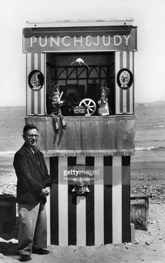 Ernest Brisbane stands on the beach next to a portable Punch and Judy puppet theater booth.