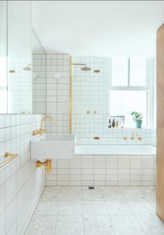 The bathroom was creatively composed using inexpensive Quarella Calacatta floor tiles, a Villery & Boch wall-mounted sink, and a Reece Sabine bath. Brass electroplated fixtures and FLOS Mini Glo Ball wall lights add a touch of sass to an otherwise understated space.