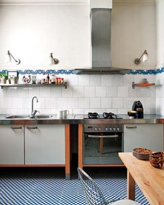 white tile, blue accent, stainless counter, lighting sconces