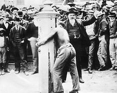 """CRIME AND PUNISHMENT:  This is a restoration of an """"original postcard from the early 1900's depicts a Black man tied to a whipping post in Delaware. Whipping posts were used for punishment by public humiliation and physical abuse, sometimes lethal. These punishments generally lasted for hours. As part of the the punishment, crowds would throw garbage, rocks, hit, kick and spit on the """"offender"""". Dover, Delaware 1910."""