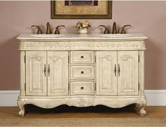 The Petriano Double Bath Vanity is an elegant addition to any master bathroom. The finish on this vanity is hand-painted with a white-cream tone that is neutral yet flavorful.  The tones are not so domineering that it overshadows other features in your overall theme.  Antique brass hardware and hand-crafted details give this provincial vanity  it's charming style and character. The countertop is cream Marfil marble and is pre-drilled with three faucet holes.  $1,299.00.