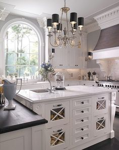 White kitchen design- Judy the knobs & handles. Notice the grey wall paint. Maybe it's a dark wood counter top?