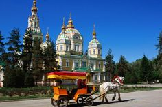Horse with cart in front of tsarist-era wooden Russian Orthodox church.~ Kazakhstan