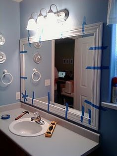 Framing bathroom mirror- love this project, just wish the hubby would cooperate in giving a girl a hand