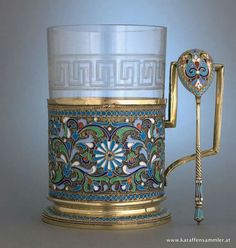 enamel Russian tea glass holder (podstakannik) in floral pattern in shades of blue and green, with matching spoon, holding clear glass with Greek key pattern decoration