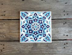 This beautiful ceramic tile is hand painted in two shades of blue. There is a hook attached to the back to hang it on the wall. There is a stamp on the back that says, Ceramics Hand Made in Greece. You could start a collection of tiles on a wall or perhaps use it as a trivet or spoon rest. There is a small chip on the back upper righthand corner but it cant be seen from the front.  It measures 6 x 6.  P.S. All of our stores items are vintage and come in vintage condition. We do our best to…