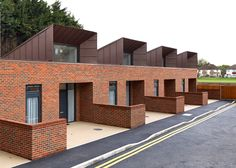 Hooded roofs funnel natural light into these brick houses in London by Bell Phillips, which provide cost-effective homes for elderly and disabled residents