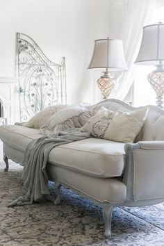 5 Tips For Simple Elegant Winter Decorating. French design with whites and grey and lots of texture via pillows, chunky throw, grey candles and marble are key for this living room styling.