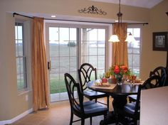 Bay Windows Design : Sliding Door Window Treatments With Curtains And Curtain Rod For Bay Window With Beige Walls And Black Dining Table With Black Dining Chairs On Tile Floor With Chandelier  Breakfast Room