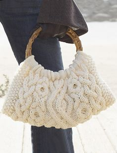 Beautiful bag in classic knitted cables. Measures approx. 16 inches (40.5 cm) wide by 8 inches (20.5 cm) tall, excluding handles. Shown in Patons Canadiana Aran (#00104) knit using sizes 5 mm (U.S. 8) and 6.5 mm (U.S. 10-1/2) needles. (Patons Yarns)