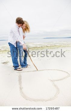 stock photo : A caucasian couple in love drawing a heart sign on the beach