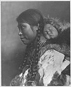 "An Eskimo mother is shown in profile with her child sleeping on her back. ""Eskimos contracted and died from influenza in disproportionately high numbers."" [Credit: The Library of Congress]"