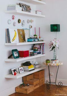 Estante branca decorada com discos, livros e objetos do cervo da moradora.
