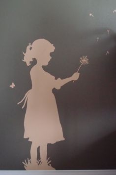 Child silhouettes on the walls using a light to trace the shadow, then filling it in with lighter paint.