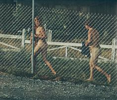 Two naked hippies behind the fence at Woodstock