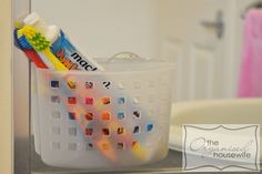 Kid toothbrush storage idea: use a plastic suction bin and stick it on the mirror. The toothbrushes will air dry, the container is easy to clean, and you can wipe the vanity top without having to move the container.