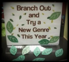 A nature-inspired sign and simple table display for January at the Main Library filled with various genres of books. | Hafuboti