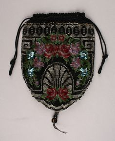 Date Made: 1915-1920  Description:  Purse; beaded rose and geometric designs in black, clear, red, pink, and green, drawstring. Black and clear ground with Greek key and fan shaped motif. A swag of roses arches above fan motif, overlaying Greek key border. Two additional roses at base of fan shape. Purse is completely beaded except for the black crocheted top through which the black cord drawstring is inserted. Small ball and beaded tassel at bottom edge of purse. Lined in navy blue cotton.