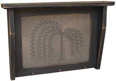 """Our Willow Tree Shelf is a black wood shelf with a distressed finish. On the front panel of the shelf there is a tin insert with a punched design of a willow tree. Shelf includes 3 metal nails across the bottom as hangers. Size of the Willow Tree Shelf is 14""""H x 20""""W."""