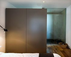 """""""the bedroom has an ensuite, concrete-rendered wetroom with frosted-glass screens, and a large wardrobe on casters that acts as a dividing wall"""""""