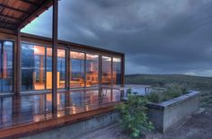 The house rests just below the crest of a gently sloping hilltop and commands powerful views. Its transparency and small size aim to minimize its impact on the land.