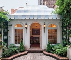 A quiet rear courtyard leads to a lovely garden pavilion. Topped with a tentlike roof, the folly would make an ideal office, guest room, or entertaining space.