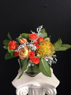 Filled with various shades of deep orange, this arrangement is truly unique. This arrangement combines spray roses, orange tulips, helios roses, pincushion protea and assorted greenery.