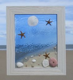 Unique beach window art by Luminosities! Lovely ocean scene with real sand, sea urchin, sand dollars, starfish and shells, with a stained blue, ocean background. Measurements are 10.5x12.5