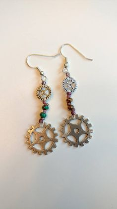 Silver Gears of two different sizes. 11/0 multicolor seed beads, and green-gold beads. Attached to silver hook earring.