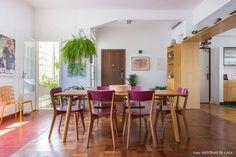 Sala de jantar integrada em apartamento recém-reformado. Móveis de madeira e cadeiras coloridas.