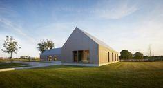 Reduziertes Landhaus mit glatten puristischen Oberflächen