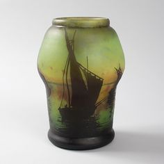 """A French Art Nouveau cameo glass vase by Daum, featuring a harbor scene with boats, and the setting sun in the background.Vases with similar decoration are pictured in: Daum, by Clotilde Bacri, Noël Daum and Claude Pétry, Paris: Michel Aveline Éditeur, 1992, p. 117  Artist: Daum  Signed:  """"Daum Nancy"""", with the Croix de Lorraine."""