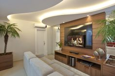 Sala de TV com sanca de gesso iluminada e painel MDF na parede. https://www.homify.com.br/livros_de_ideias/31002/7-salas-de-tv-incriveis-para-a-sua-casa