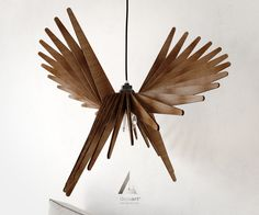 modern wooden handmade pendant light lasercut that looks like a bird. Made with 4 mm plywood (all scraped with sandpaper and varnished 3 times)
