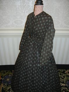 Print Wool Dress c.1861-63   photographed at the Conference    Interesting print of two toned double rings, white and teal on dark brown. Pleated bodice with slight V to the jewel neck, edged with tape; front opening with hooks and eyes. Waistband with left offset; knife-pleated, unlined skirt, with deep hem facting, and black hem braid. Sleeves with tape at cuff.