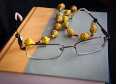 """Do you have trouble keeping track of your glasses? These colorful """"leashes"""" are a great way to make sure your glasses are close at hand at all times. Each leash is made out of handcrafted paper beads and coordinating glass seed beads. The two loops on the end make them easy to slip on and off glasses. www.haitianbeads.org"""