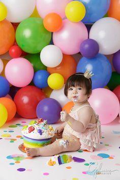 Orange County cake smash photographer, little, girl, eating, cake, hat, headband, rainbow, colorful, backdrop, background, pink, purple, blue, yellow, sitting on the floor, GilmoreStudios.com