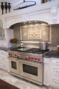 "Yes this has a beautiful tiled backsplash but we noticed the exceptional detail of how the base columns on each side of the 48"" Wolf Dual Fuel Range matches exactly to the edge of the range. Now that is a Kitchen Design Detail we love!  http://www.mrsgs.com/products/wolf/df486g.html    photo compliments of astepinstone.com.    This is the range I dream about putting in my new kitchen."