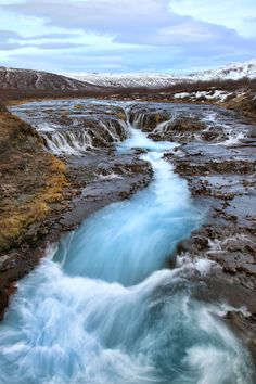 Cascades and a raging turquoise river can be seen in the Golden Circle area of Iceland in winter.